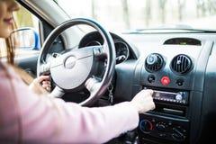 妇女在汽车的设定音乐 汽车控制台控制板电子仪器航海 无线电特写镜头 妇女设定了收音机 库存照片