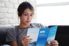 妇女在沙发的读书旅行Flye在家 免版税库存图片