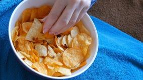 妇女在沙发说谎在一条蓝色毯子下并且吃从一块深板材的土豆片 不健康的食物,快餐 影视素材