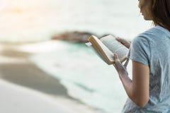 妇女在沙子海滩的阅读书 库存图片