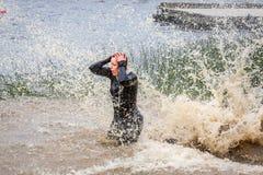 妇女在泥泞的飞溅的水中 免版税库存照片