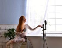 妇女在浴缸水龙头附近坐准备好采取浴近开放卫生间窗口饮料茶或咖啡 库存照片