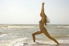妇女在海实践瑜伽和凝思在英雄位置在海滩 库存照片