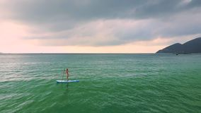 妇女在海洋中的paddleboard乘坐海浪 影视素材