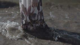 妇女在海海滩的白色花服站立在波浪泡沫在夏天晴天平的颜色 影视素材