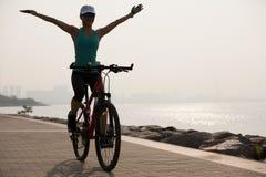 妇女在海边的骑马自行车 库存照片