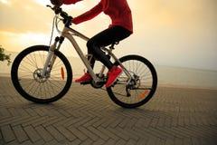 妇女在海边的骑马自行车 免版税库存照片
