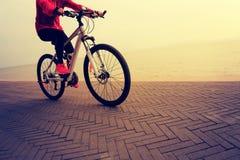 妇女在海边的骑马自行车 免版税库存图片