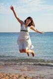 妇女在海运海滩跳 库存照片