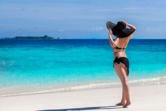 妇女在海滩停留并且观看在海 库存照片