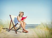 妇女在海滩放松概念的阅读书 免版税图库摄影