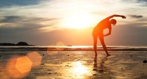 妇女在海滩的剪影锻炼在日落 体育运动 免版税库存照片