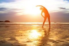 妇女在海滩的剪影锻炼在日落 免版税库存图片