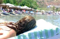 妇女在海滩睡椅放置 免版税图库摄影