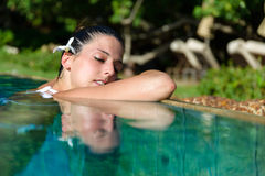 妇女在温泉室外极可意浴缸的水池放松 免版税库存图片