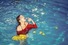 妇女在温泉水池放松 妇女用在水池的热带水果 在香蕉的维生素在坐在水附近的女孩 节食和 免版税库存照片