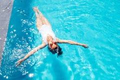 妇女在游泳水池放松 豪华旅游胜地假期 免版税库存照片