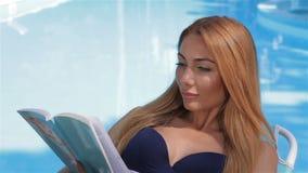 妇女在游泳池附近读书 股票录像