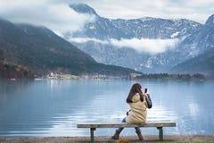 妇女在湖岸使用她的电话 免版税图库摄影