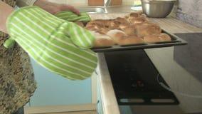妇女在火炉上去掉被用烤箱烘的酥皮点心并且把盘子放 股票视频
