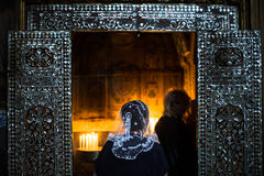 妇女在点蜡烛的教堂里祈祷 免版税库存图片