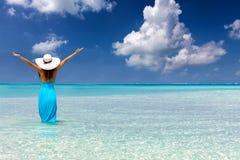 妇女在热带站立,绿松石浇灌并且享受她的假期 免版税库存图片