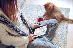 妇女在片剂的读书新闻 免版税库存照片