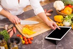 妇女在片剂的食谱后 免版税库存照片
