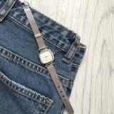 妇女在牛仔裤背景的` s手表  免版税库存图片