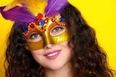 妇女在狂欢节化妆舞会面具的面孔特写镜头与羽毛,在黄色颜色背景,长的卷发的美丽的女孩画象 免版税库存照片