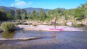 妇女在瑜伽位置站立反对有急流的河 股票录像