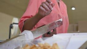 妇女在生产线附近站立,并且她是rearege玉米棍子在工厂 影视素材