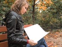 妇女在生叶通过白色册页的页的秋天公园 生叶通过页的妇女 长凳的妇女在 免版税库存照片