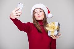 妇女在电话的作为selfie有圣诞节帽子举行礼物的 库存照片