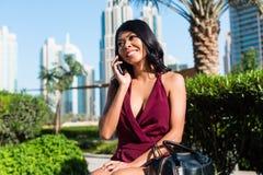 妇女在电话的城市公园 免版税库存图片