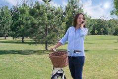 妇女在电话走与自行车并且谈话 免版税库存照片