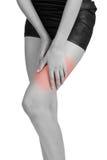 妇女在痛苦区域的拿着她的大腿 免版税库存图片