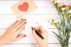 妇女在白皮书写情书用红色心脏形状无花果 免版税库存图片