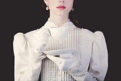 妇女在白色维多利亚女王时代的时代穿衣与茶 免版税库存照片