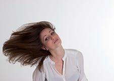 妇女在白色背景吹她的头发被隔绝 免版税库存图片