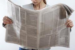 妇女在白色背景的读书报纸 图库摄影