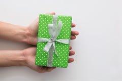 妇女在白色背景递拿着绿色礼物盒被隔绝 顶视图,平的位置 Copyspace 库存照片