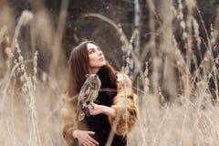 妇女在皮大衣的秋天有猫头鹰在手边第一雪的 有长的头发的美丽的深色的女孩本质上,拿着猫头鹰 图库摄影