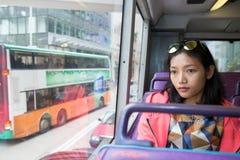 妇女在看窗口的公共汽车上 免版税库存照片