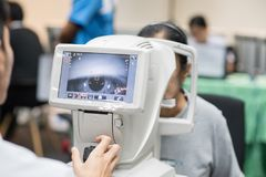 妇女在眼科学方面的看折射计眼睛测试机器 库存图片