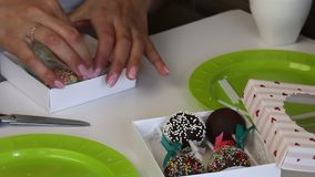 妇女在礼物盒投入蛋糕流行音乐 糖果用不同颜色选矿和丝带弓装饰 修剪剩余剪刀 影视素材