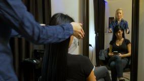 妇女在社会媒介使用巧妙的电话浏览,当坐在美容院时的一把椅子 影视素材