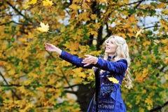 妇女在秋天公园扔五颜六色的秋叶 图库摄影
