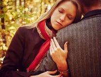 妇女在秋天公园拥抱一个人 免版税库存图片