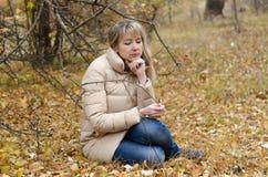 妇女在秋天森林里哀悼四十年 库存照片